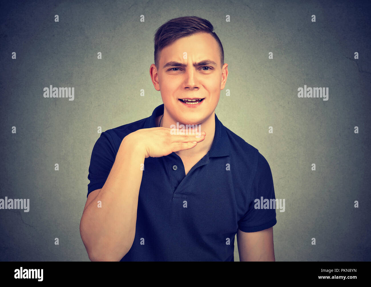 Young angry man being rude and mocking up while looking at camera negatively - Stock Image