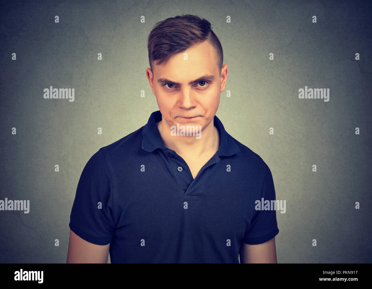 Young hateful man frowning and looking at camera in distaste on gray background - Stock Image