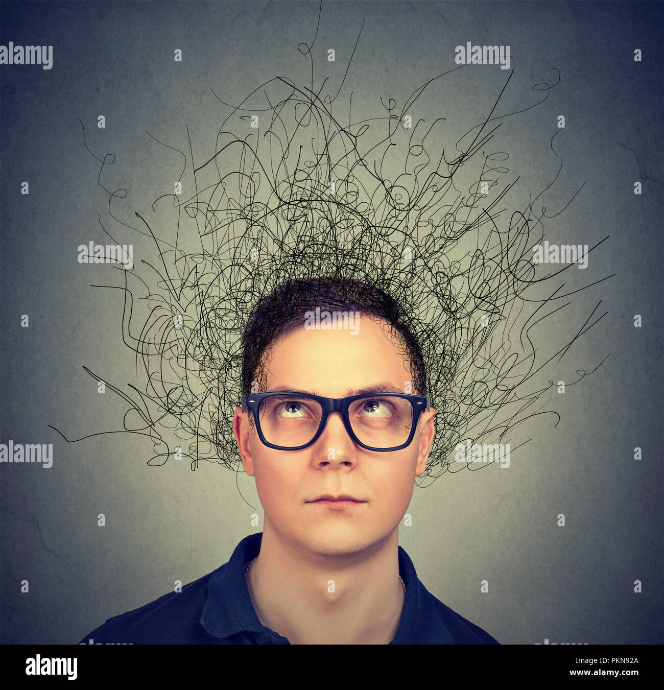 Young man in eyeglasses with thoughts in anxiety and chaos looking up on gray background - Stock Image