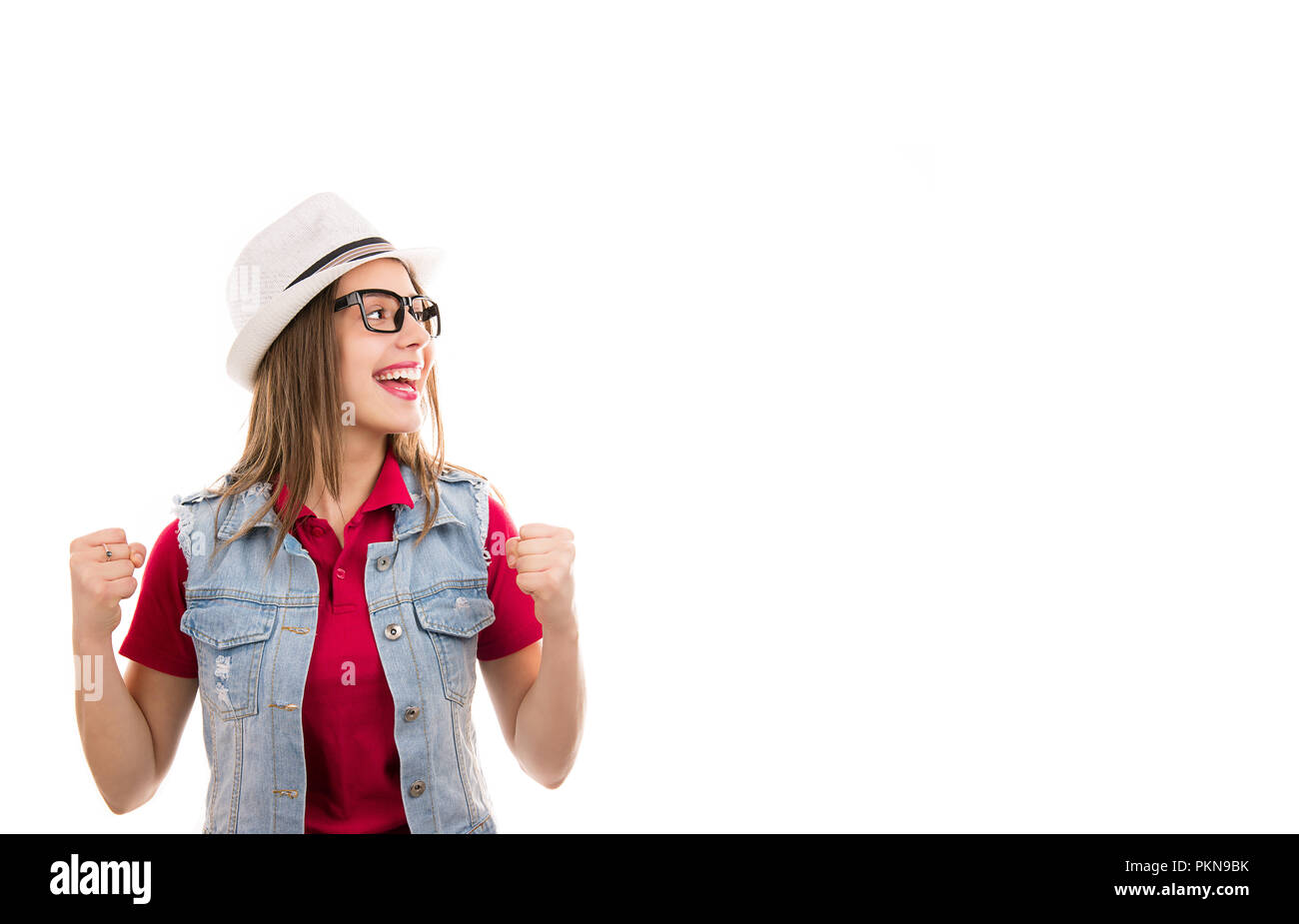 fae9bc7346af Casual young woman in hat and glasses with fists up screaming feeling  excited looking super thrilled