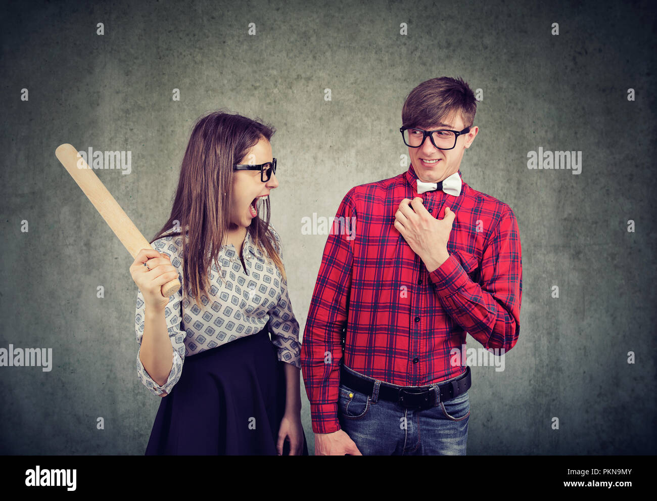 Young woman with rolling pin looking crazy while arguing with man on gray background - Stock Image