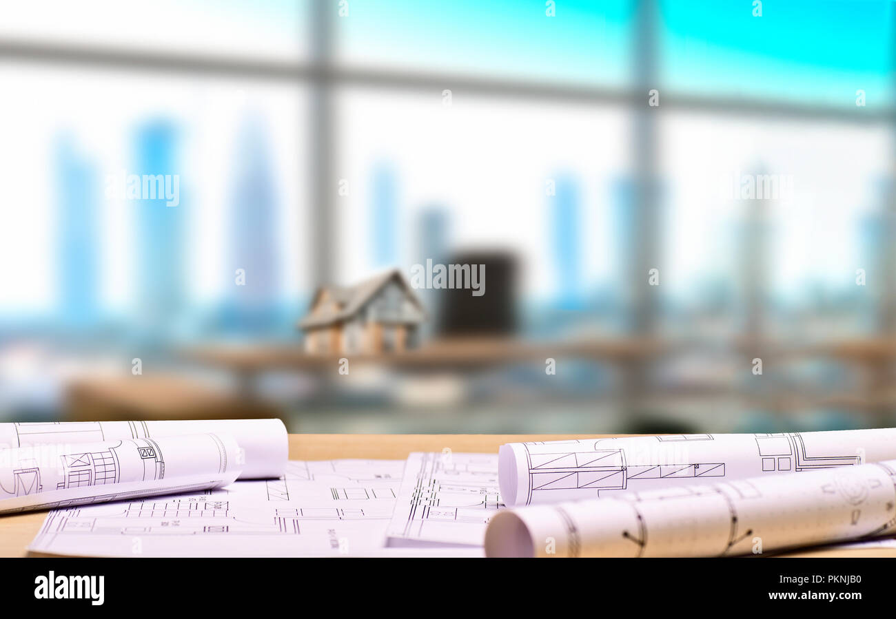 Architectural office with blueprints and an architectural model on a desk in the background Stock Photo