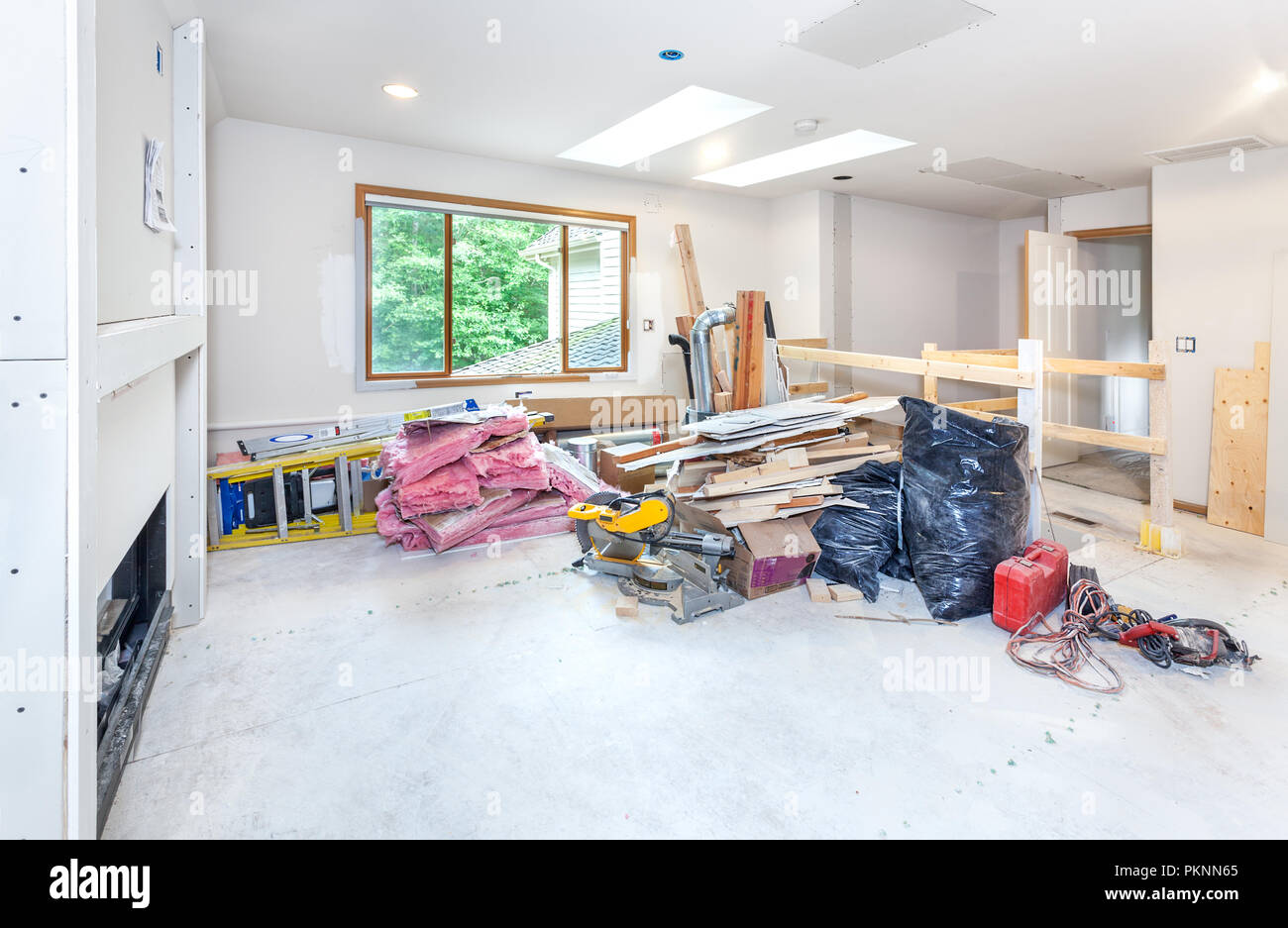 Waste wood, drywall, insulation and trash bags piled up with tools and ladders at the end of the work day - Stock Image