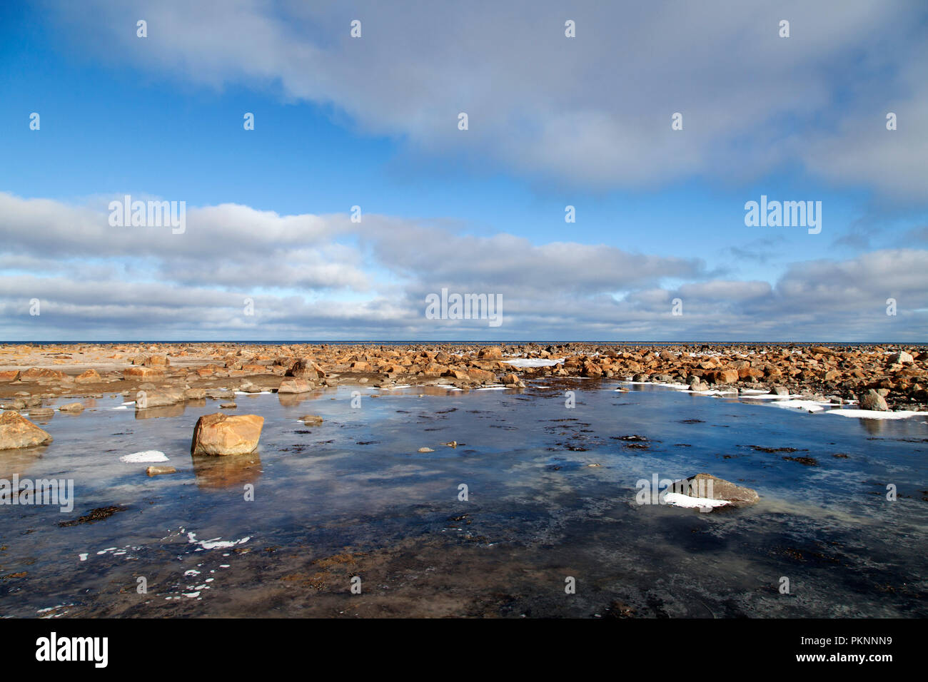Icy rocks by the shore of the Hudson Bay in Manitoba, Canada. The Bay freezes during winter. - Stock Image