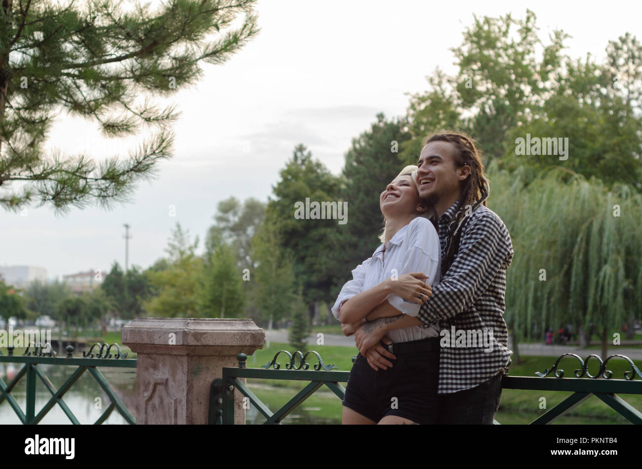 Romantic happy couple in love hugs and laughing .Attractive woman and her handsome bearded boyfriend in the park. - Stock Image