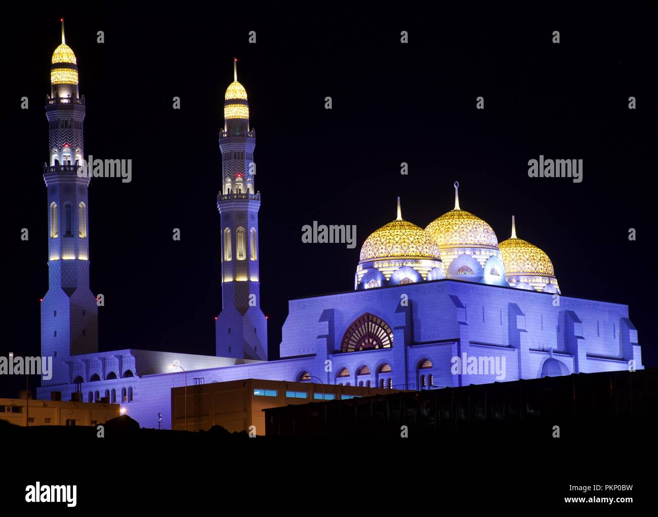 Al Ameen Mosque in Muscat, Oman shines boldly and brightly at night. - Stock Image