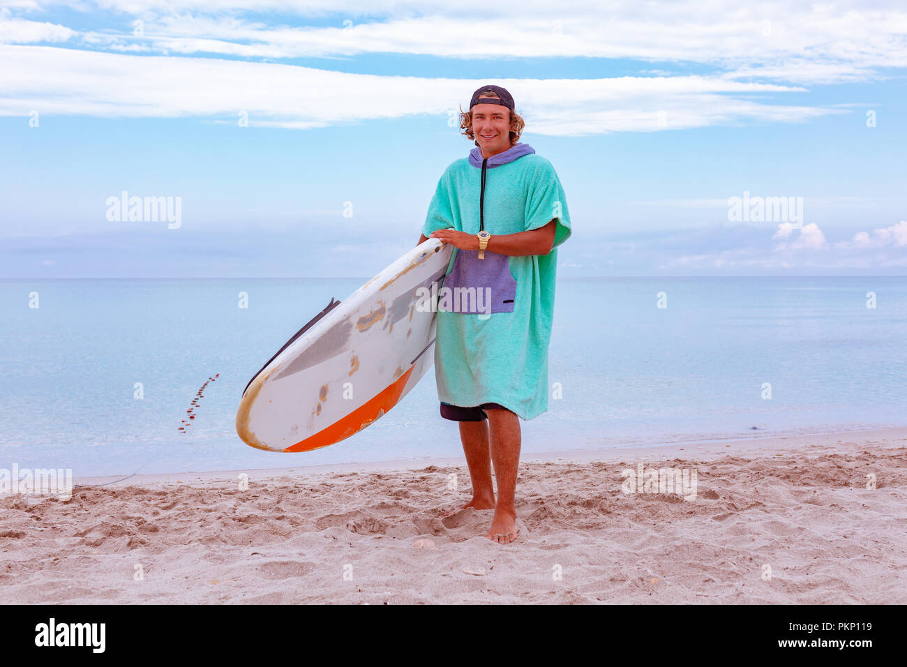 Handsome man walk with white blank surfing board wait for wave to surf spot  at sea 5018622a4