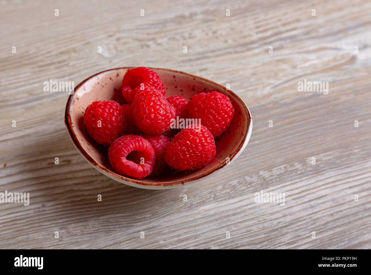 Ripe sweet raspberries in bowl on wooden table. Close up, top view, high resolution product - Stock Image