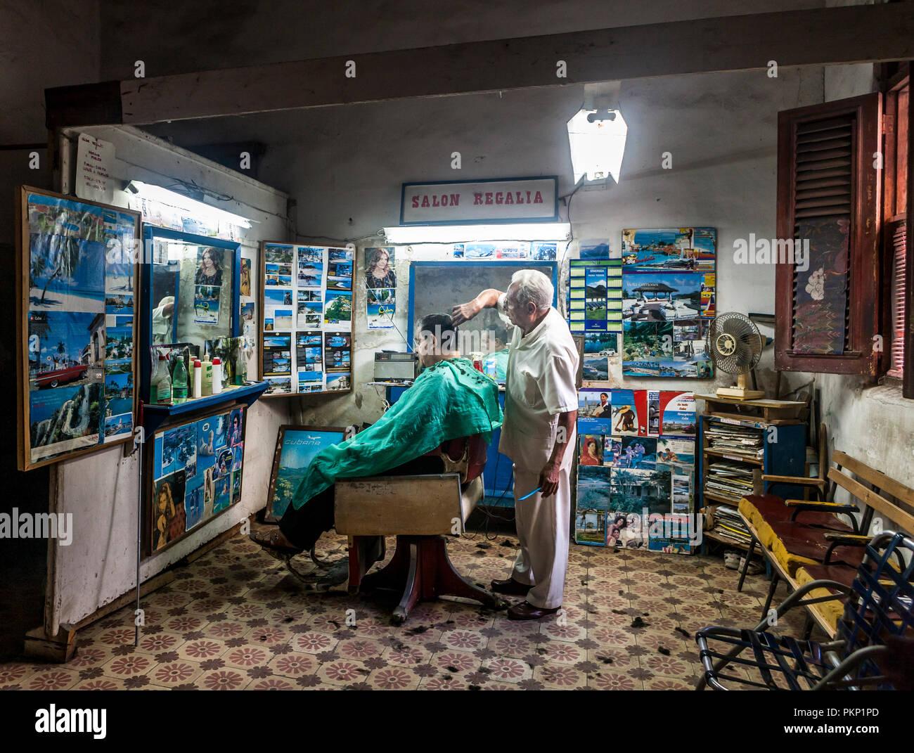 Regalia, Havana, Cuba. 22nd January 2013. A barber cuts his clients hair in his shop in Regalia, Cuba. - Stock Image