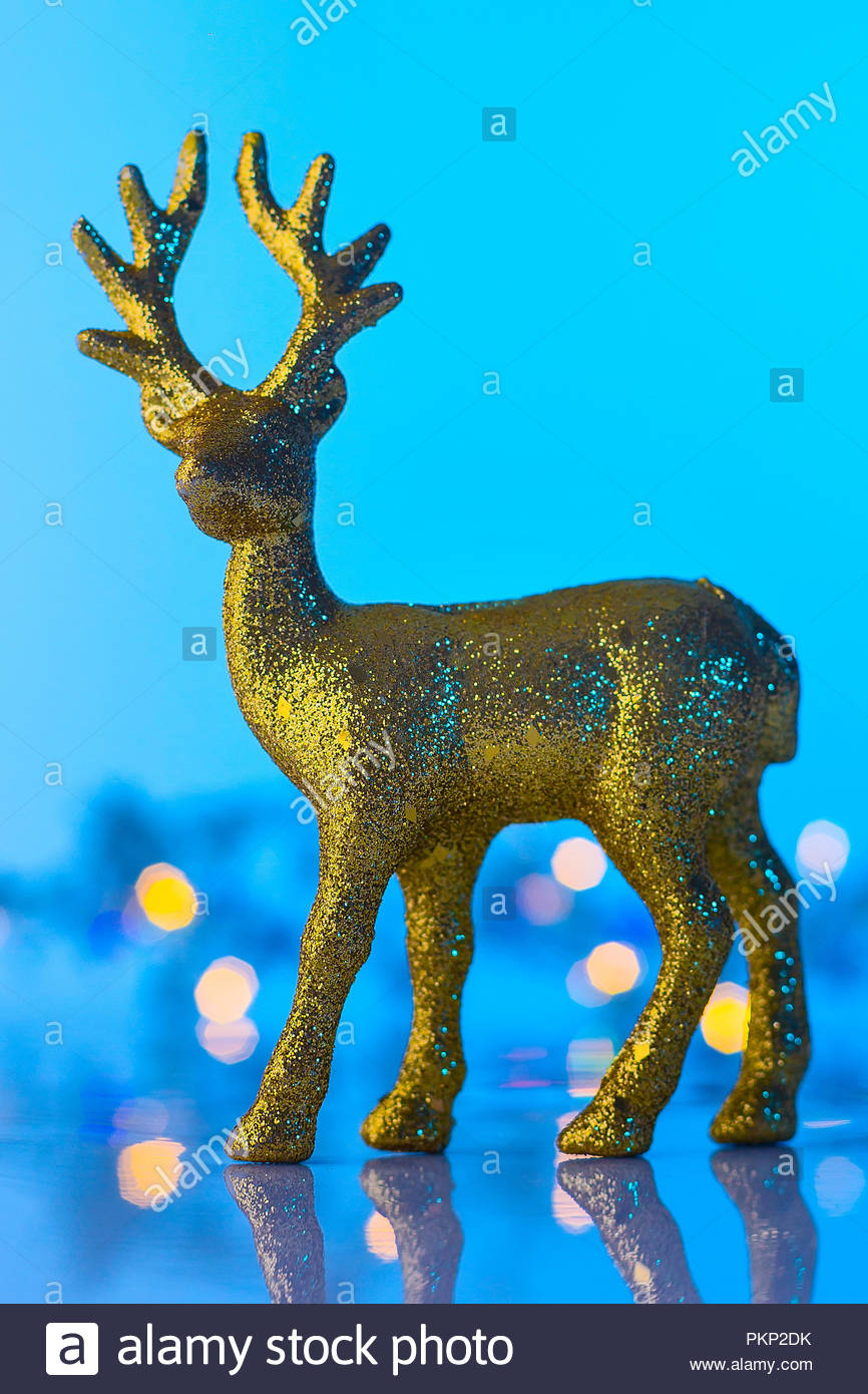 Christmas or New Year golden Reindeer, blue and turquoise bokeh background with lights - Stock Image