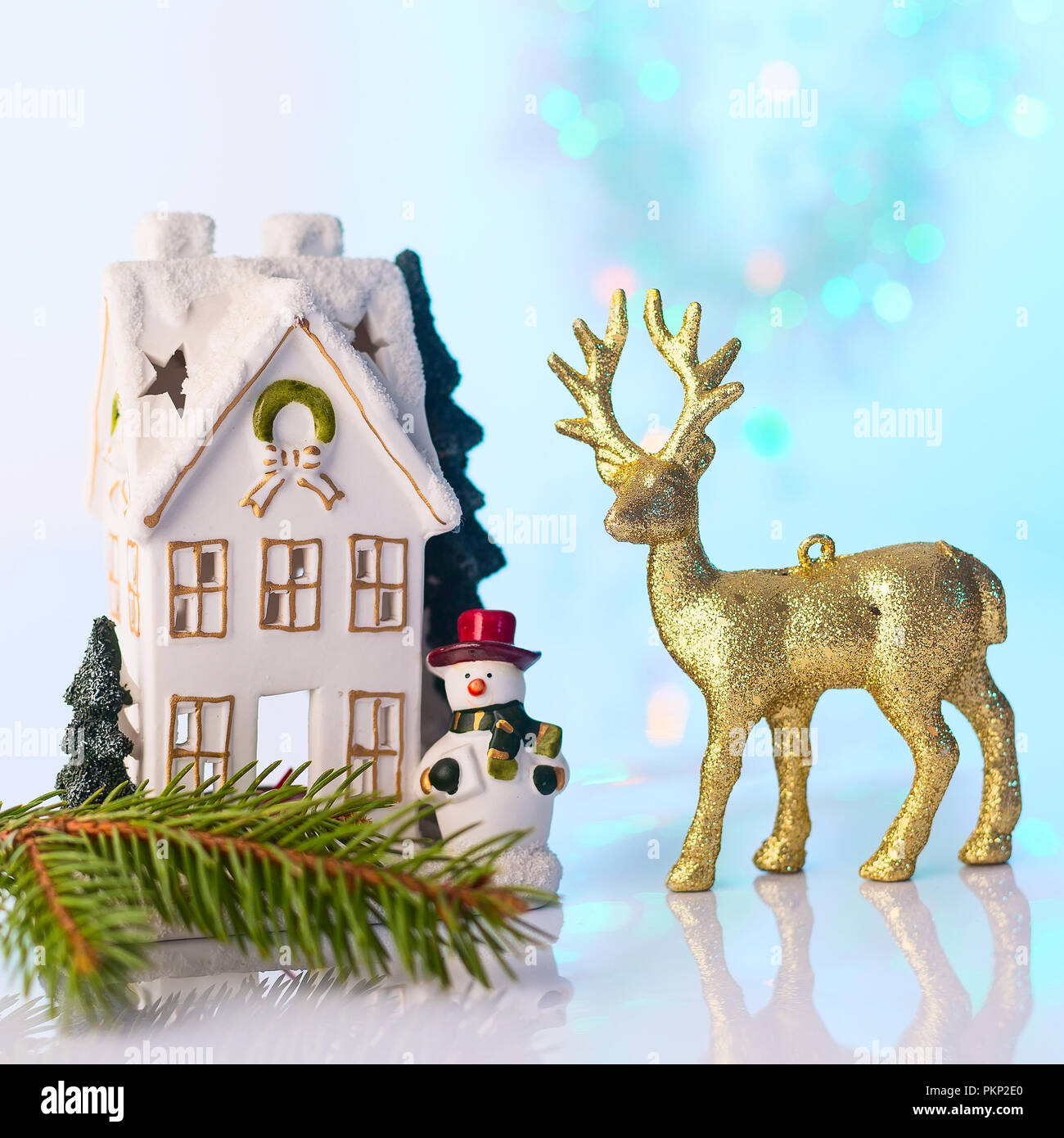 Christmas or New Year snow house, snowman and golden reindeer, blue and turquoise bokeh background with lights - Stock Image