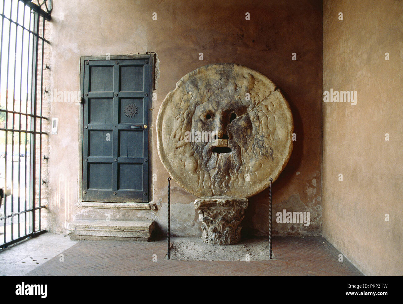 Italy. Rome. Santa Maria in Cosmedin church (former ancient prison) interior with stone carving of man's face or mask, the Mouth of Truth (Bocca della - Stock Image