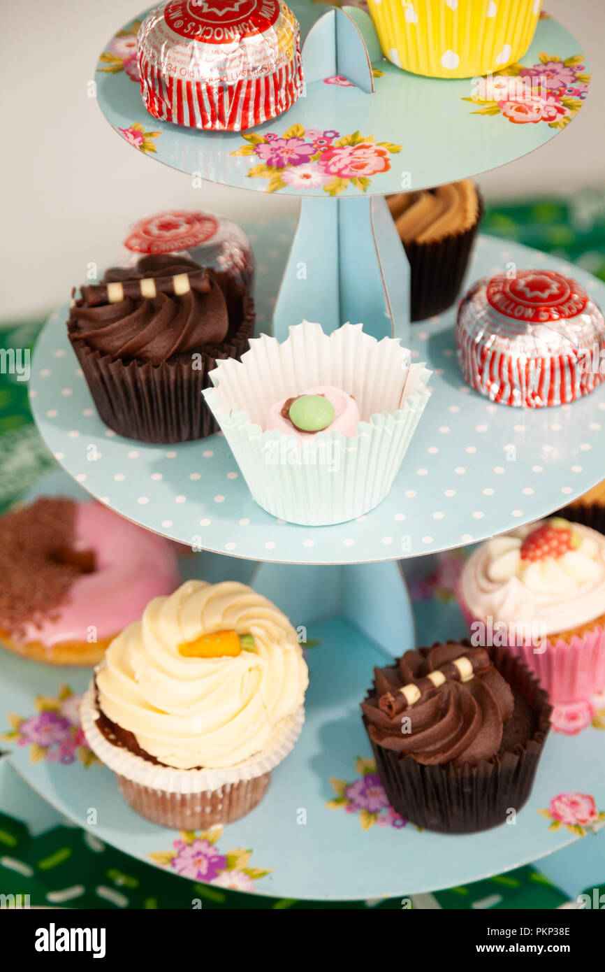 A Collection Of Cupcakes On A Cardboard Cake Stand Stock Photo
