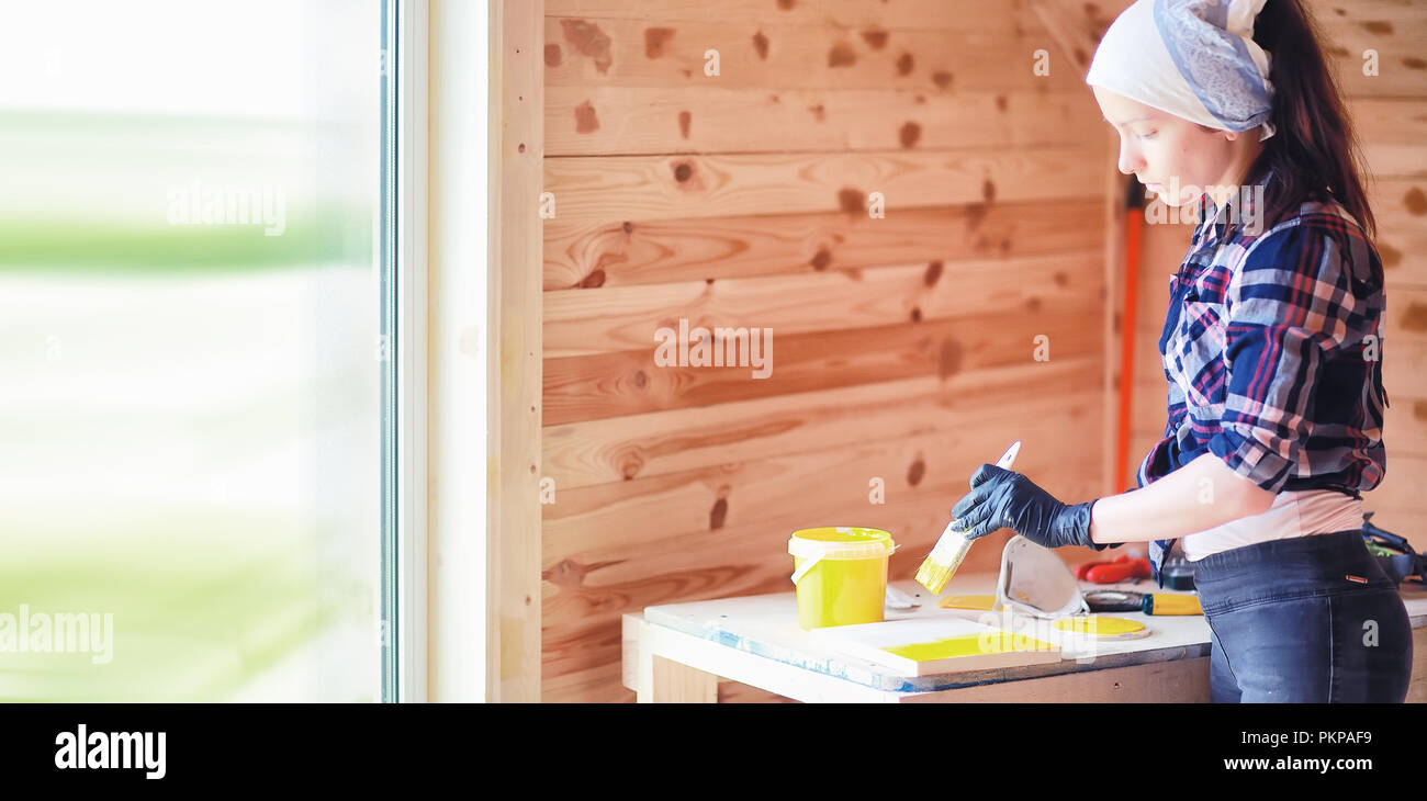 Woman with brush in a wooden house Stock Photo