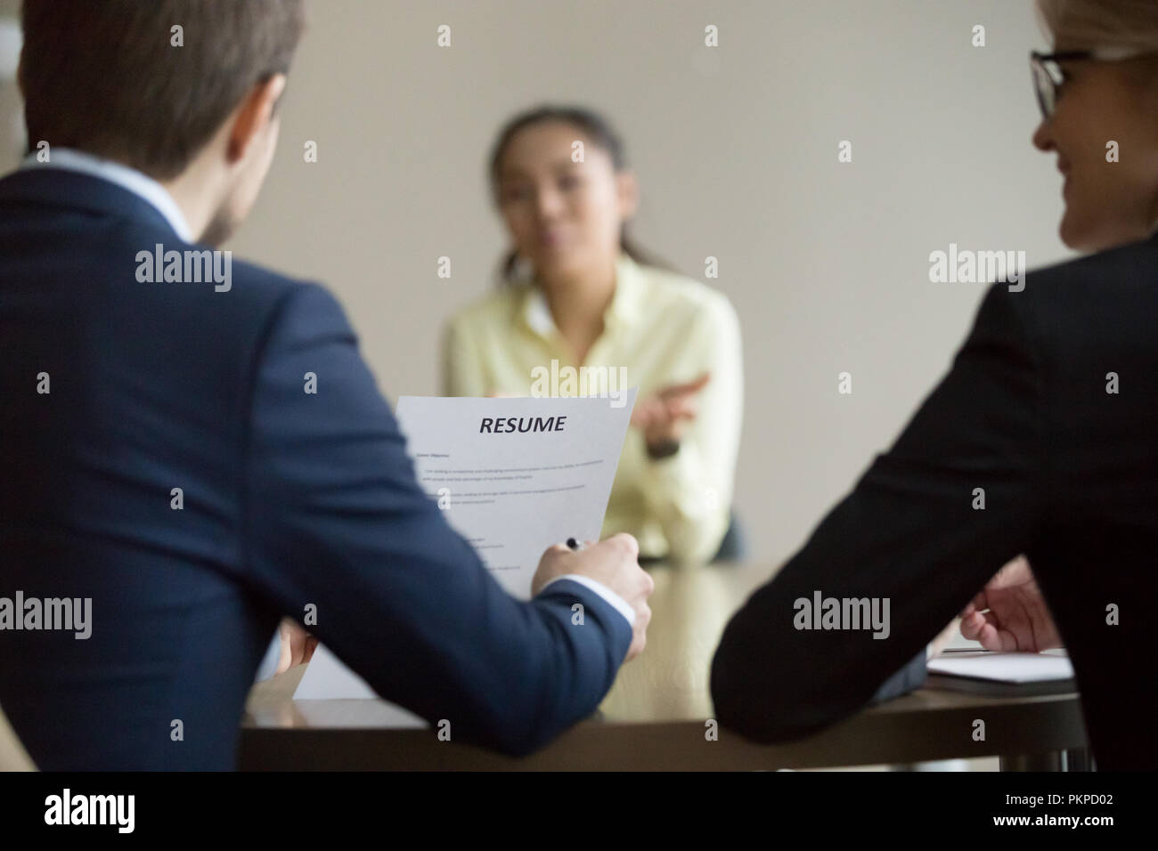 Businesswoman, businessman HR managers interviewing asian woman  - Stock Image