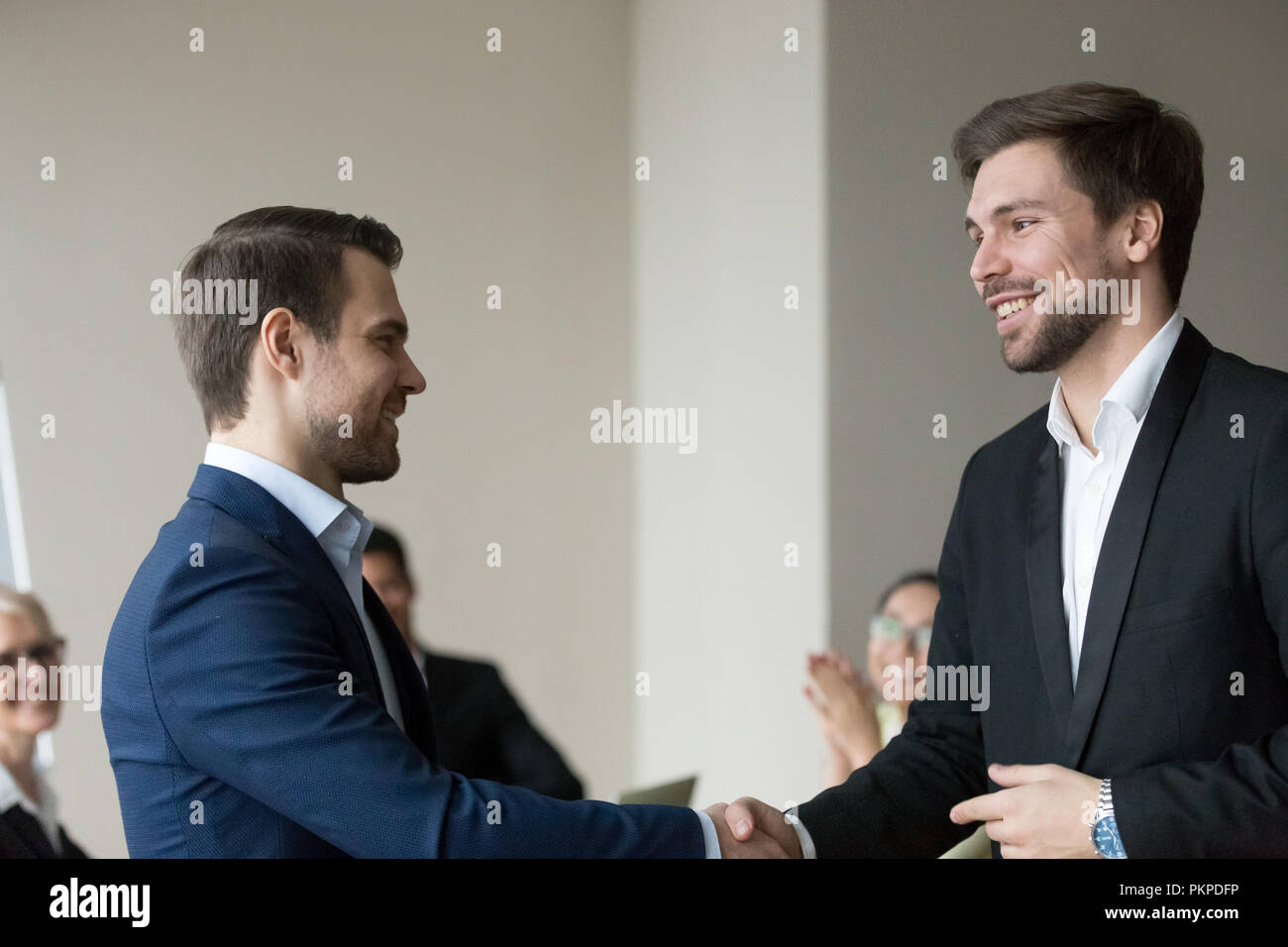 Handshake of two successful smiling happy business people  - Stock Image