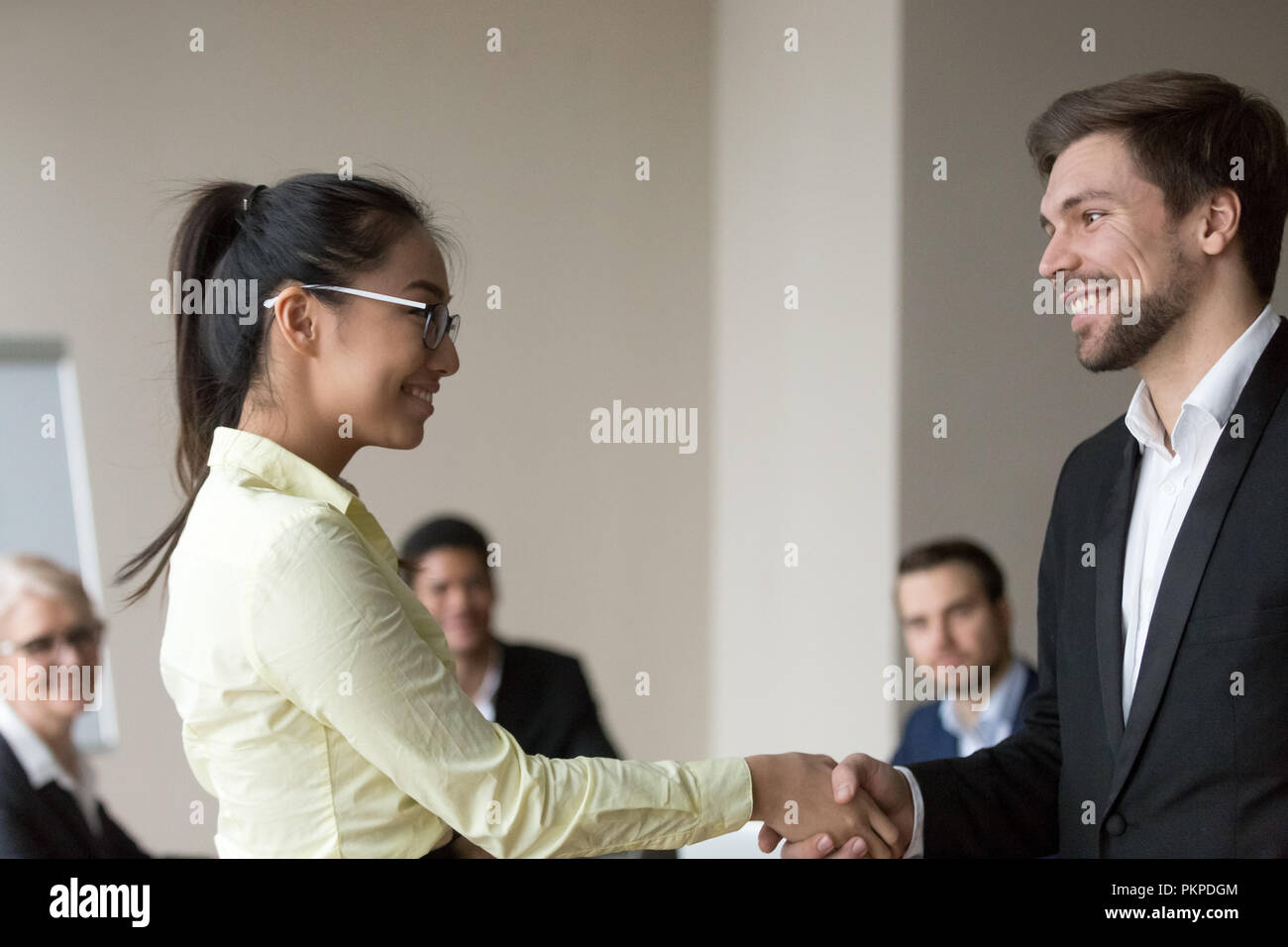 Handshake of two smiling happy business people  - Stock Image