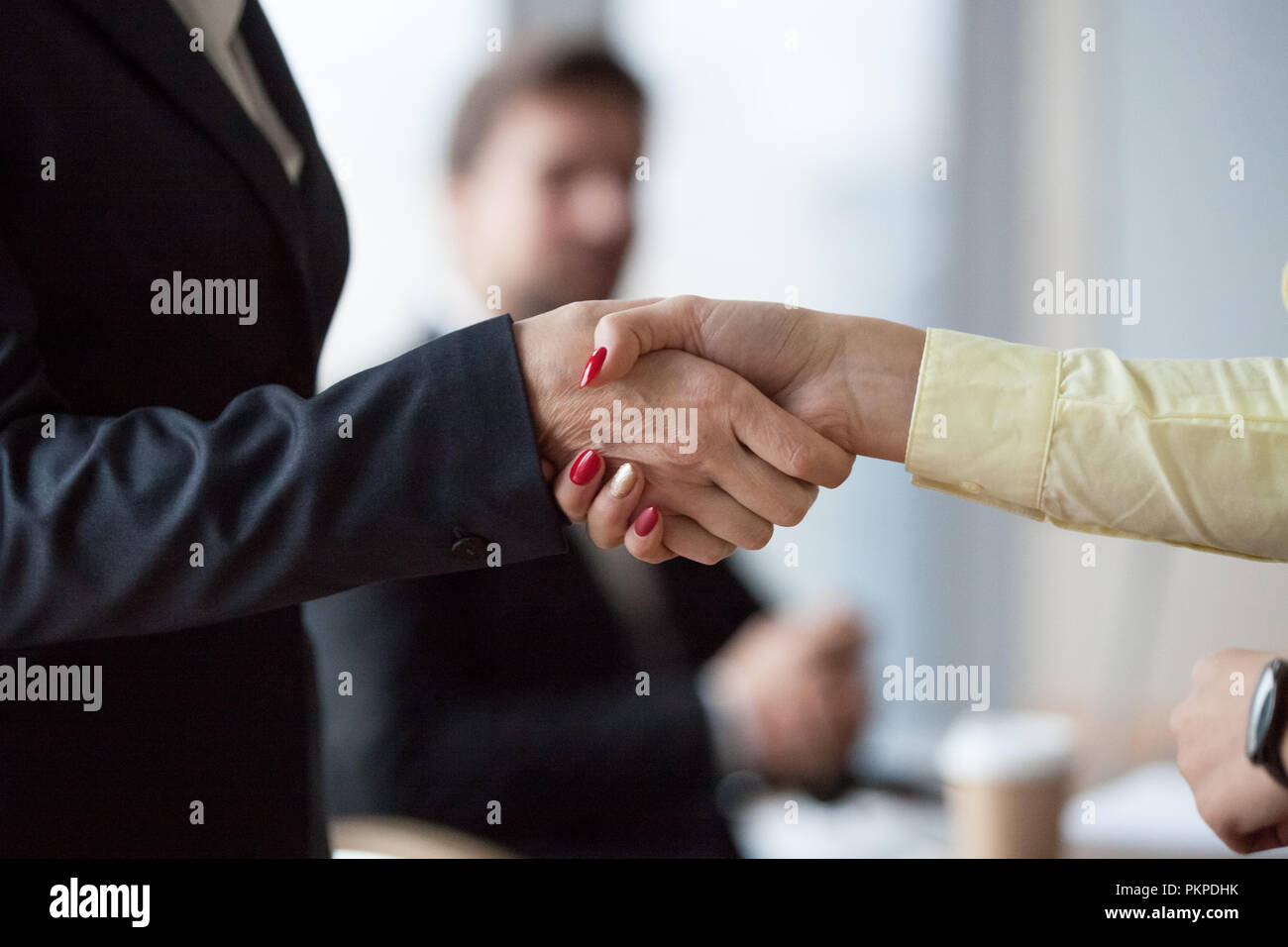 Close up of womans handshake in office  - Stock Image