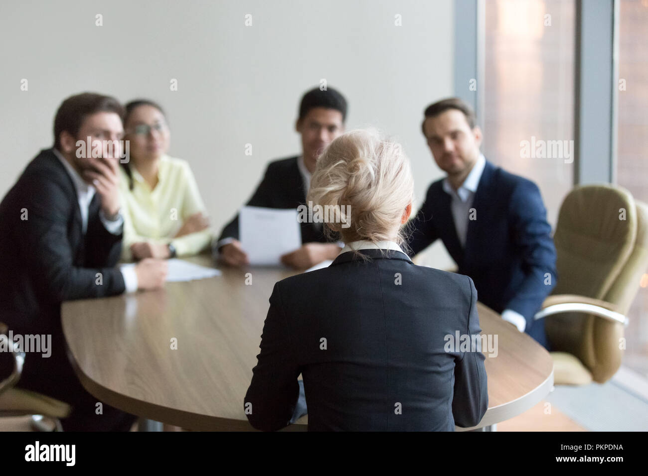 Woman passing job interview at office, interviewers on backgroun - Stock Image
