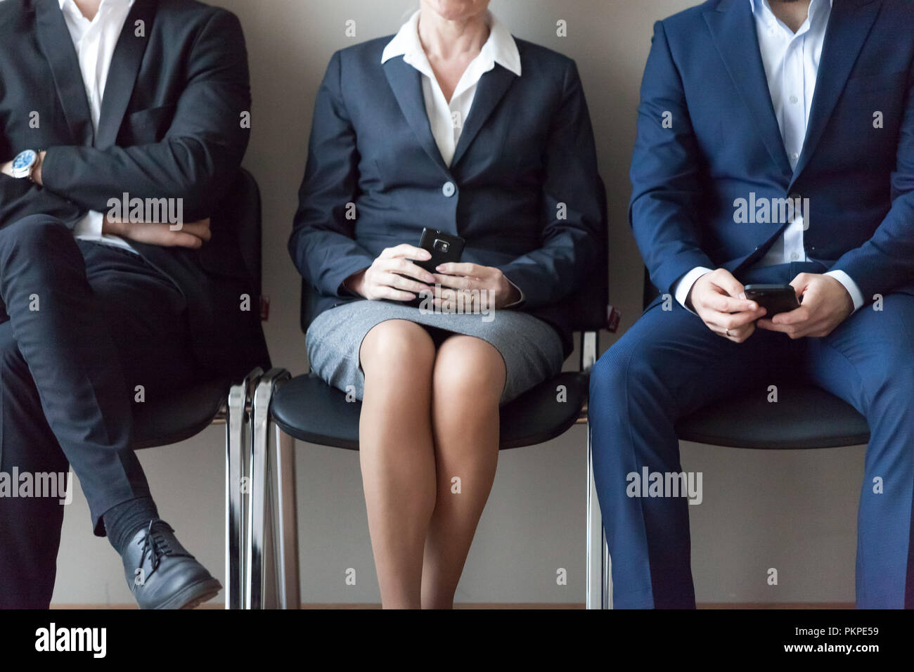 Business people sitting in chairs in queue waiting job interview - Stock Image