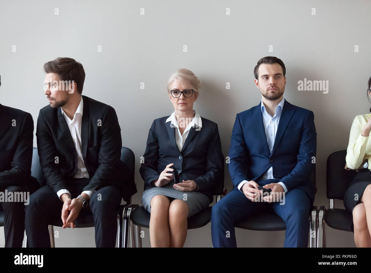 Young and mature candidates waiting for job interview in office - Stock Image