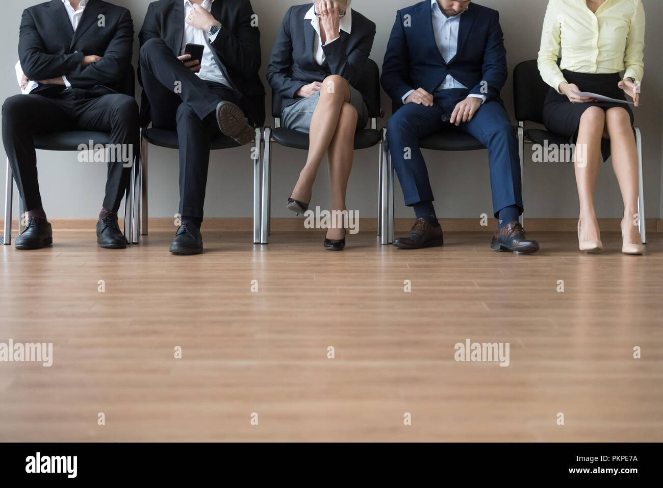 Businesspeople legs sitting in chair in queue wait job interview - Stock Image