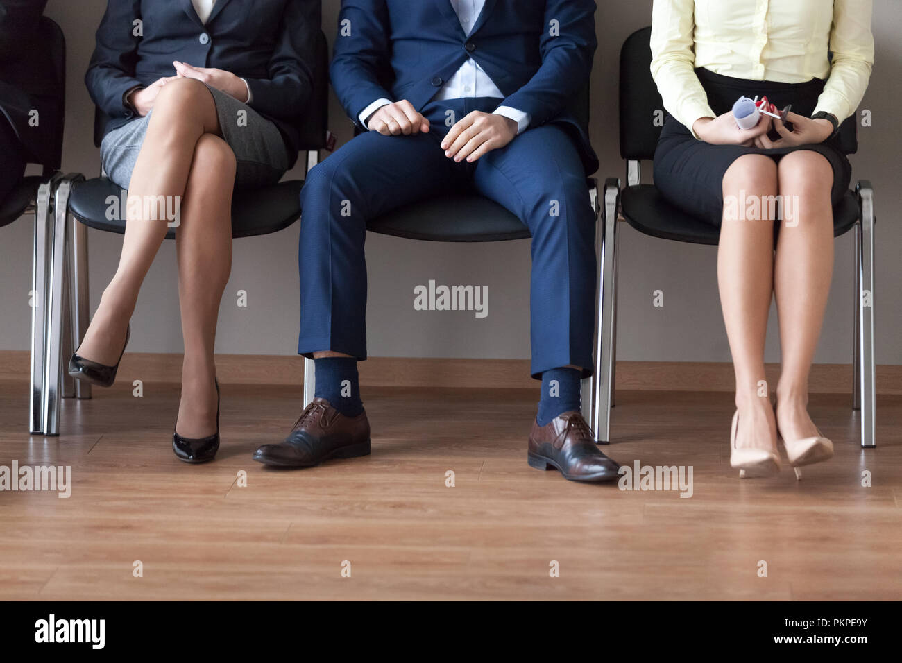Businesspeople sitting in chairs in queue waiting job interview  - Stock Image
