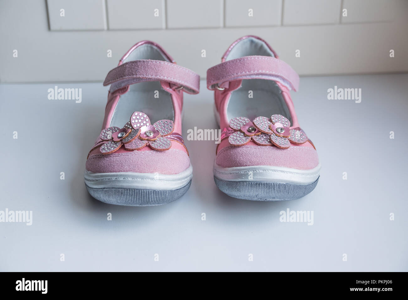 b7be9a98cad75 Pair of cute baby sandals decorated with flowers on white background ...