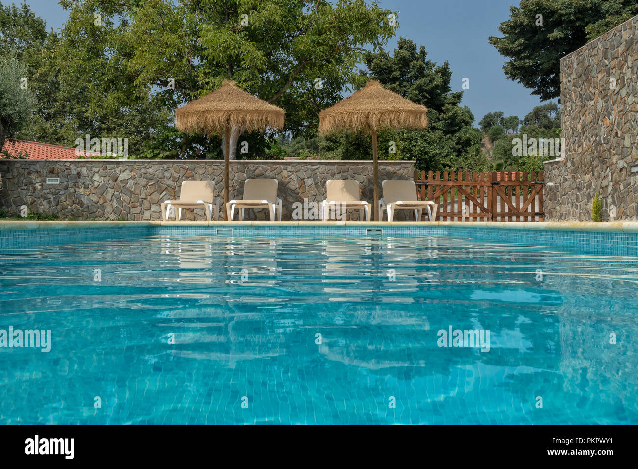 Pool view at the water level with leisure chair Stock Photo ...