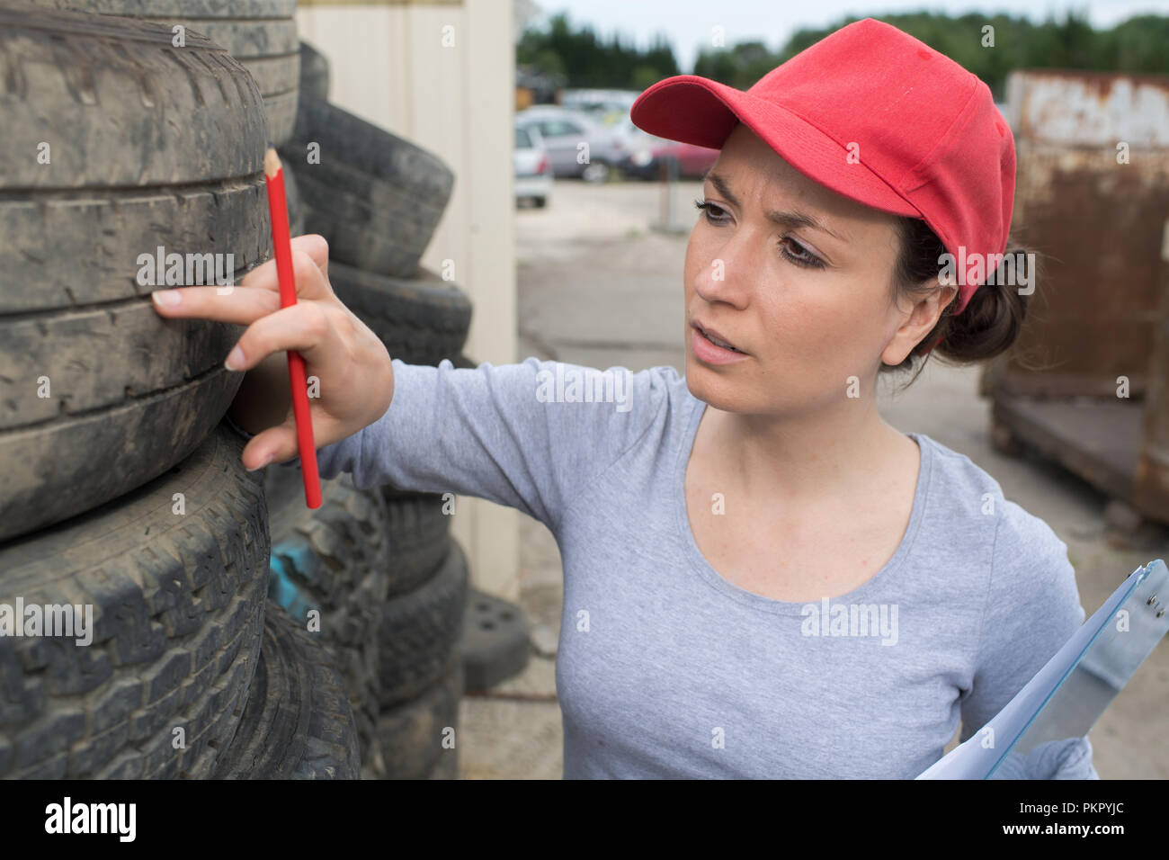 woman checking tread on car tyre with gauge Stock Photo