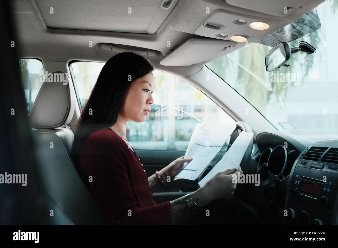 Chinese female manager working in car. Successful Asian businesswoman using laptop computer and looking at paperwork. - Stock Image