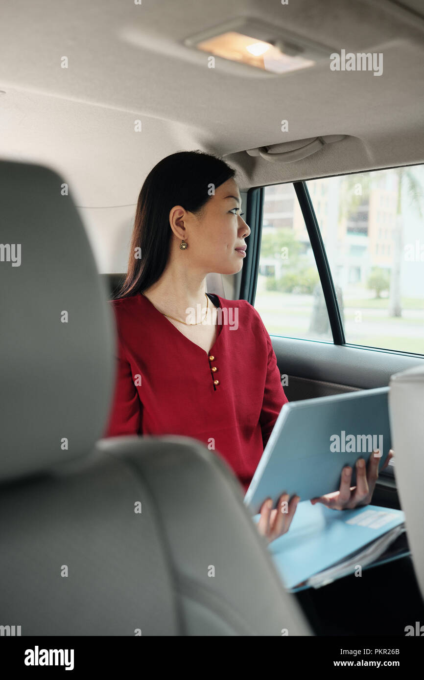 Chinese female manager working in car while commuting to work. Successful Asian businesswoman using laptop computer and riding taxi. - Stock Image