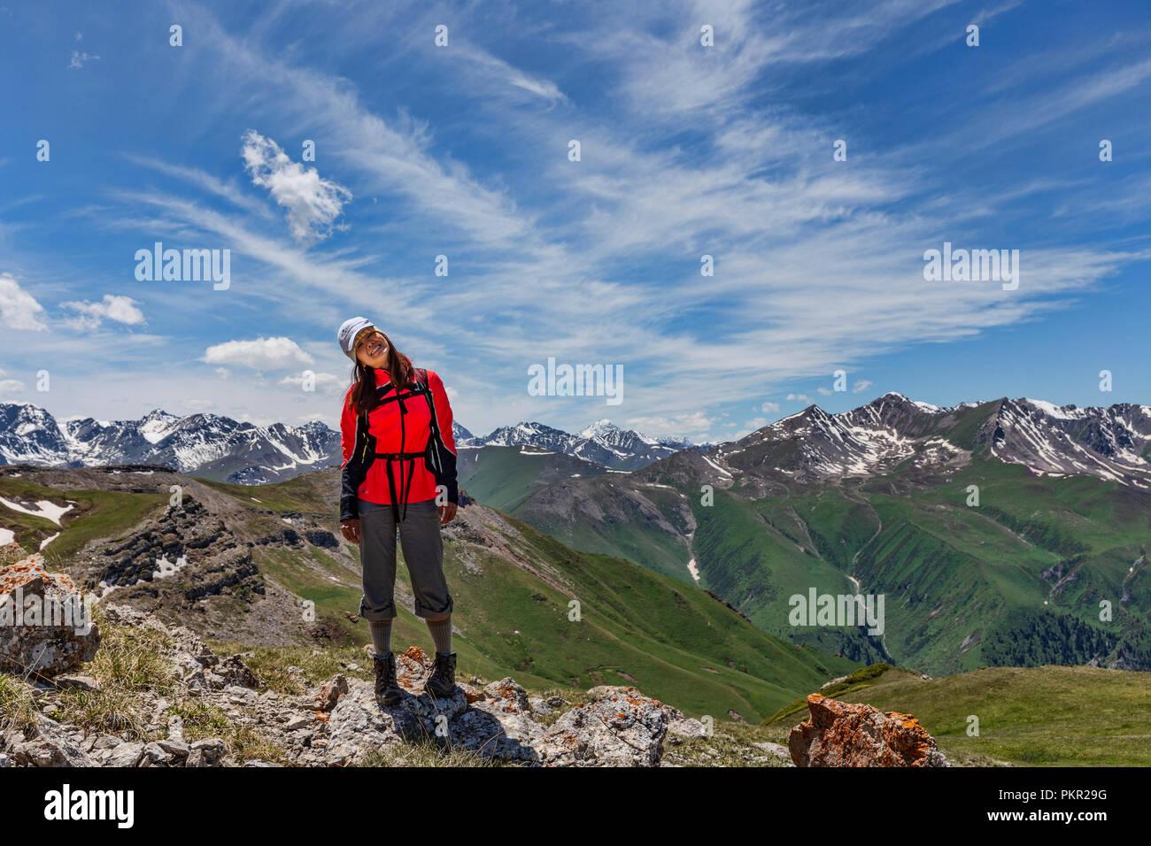 Trekker framed by Terskey Ala-Too mountain range, Anvar Pass, Keskenkyia Loop trek, Jyrgalan, Kyrgyzstan - Stock Image