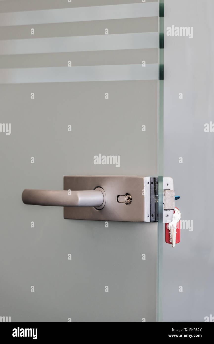 Modern glass door with metal alloy handles and key chain in lock, home or office security concept - Stock Image