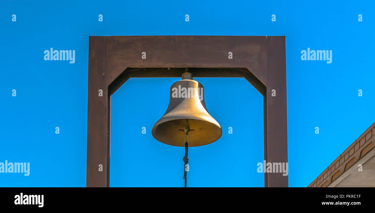 Bell with blue rope attached to a rectangular yoke - Stock Image