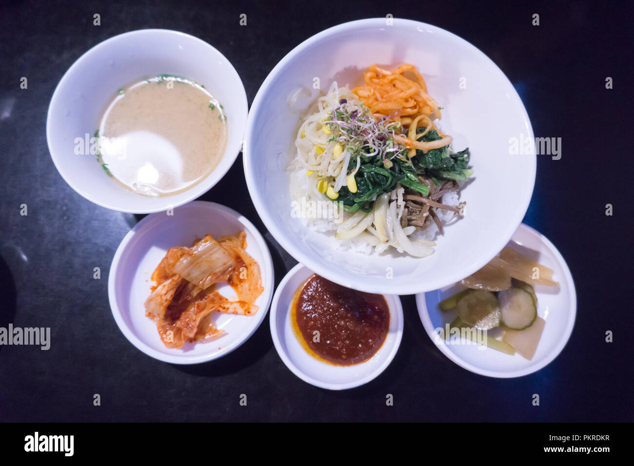 Bibimbap - Rice mixed with vegetables, meat, and chili pepper paste and side dishes from korea. - Stock Image