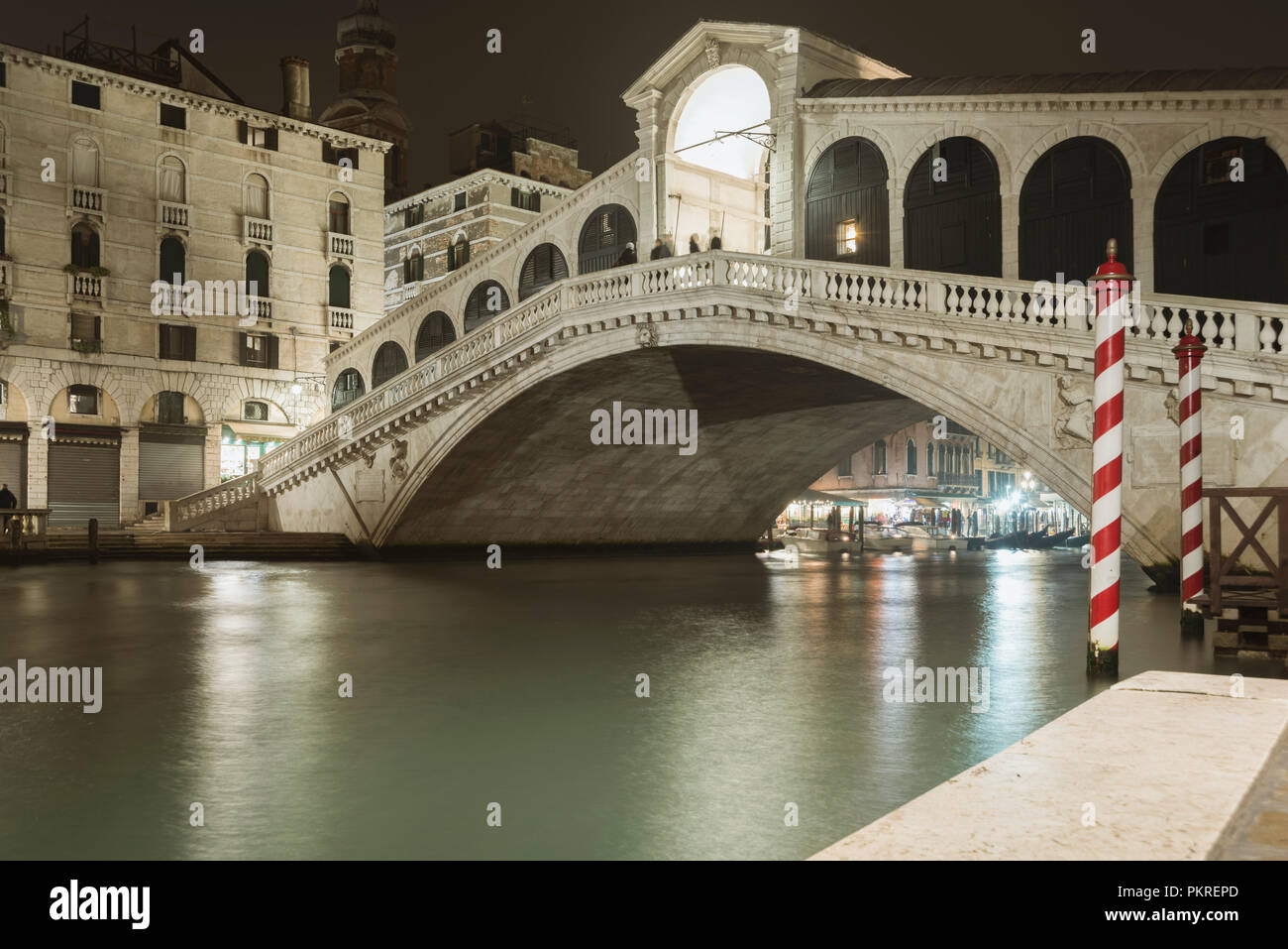 famous Rialto bridge illuminated by night above waters of Grand Canal - Stock Image