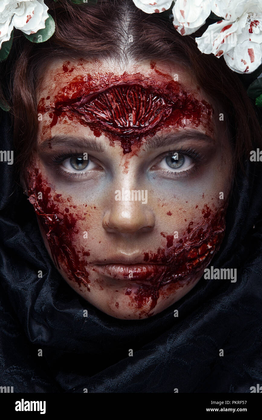 Portrait of bloody horrible scary zombie girl in a halloween festive makeup Stock Photo