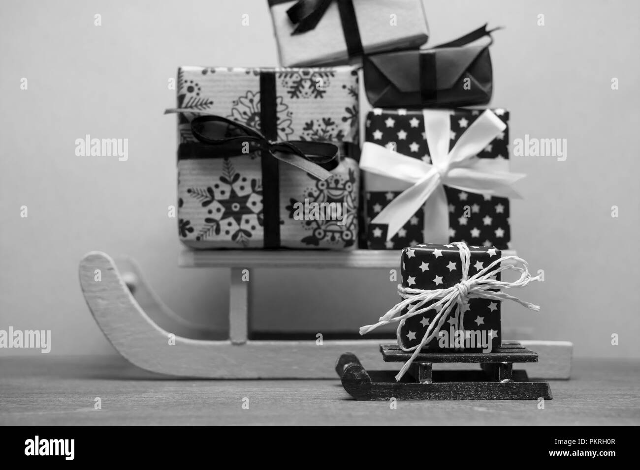blac white christmas sledges with pile of presents blue background - Stock Image
