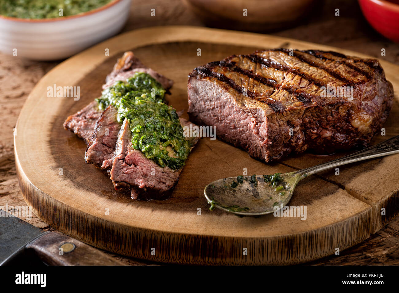 A delicious medium rare fire grilled argentina style steak with chimichurri verde sauce. Stock Photo