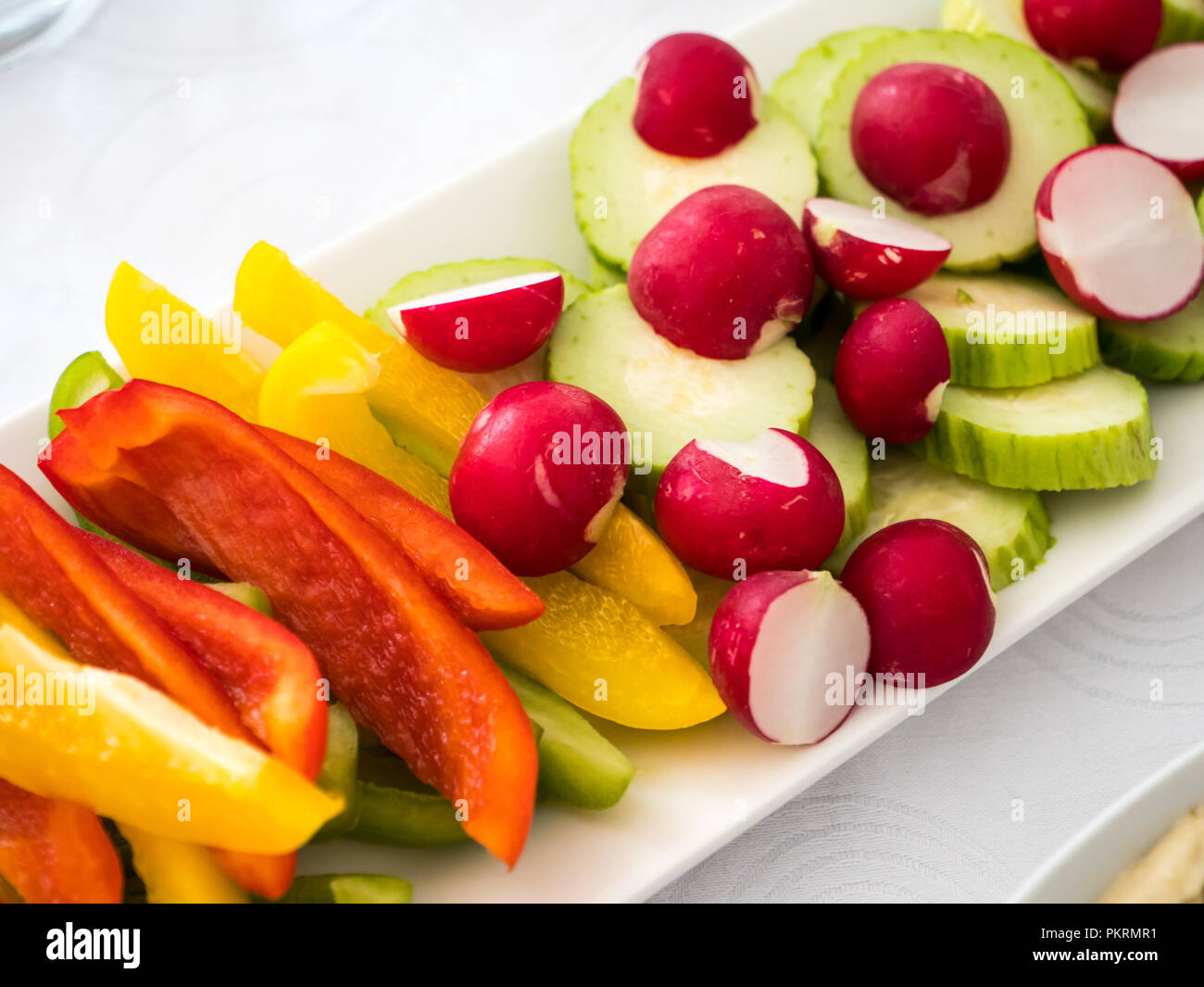Close up of a plate with mixed fresh vegetables: redish, paprika, cucumber - Stock Image