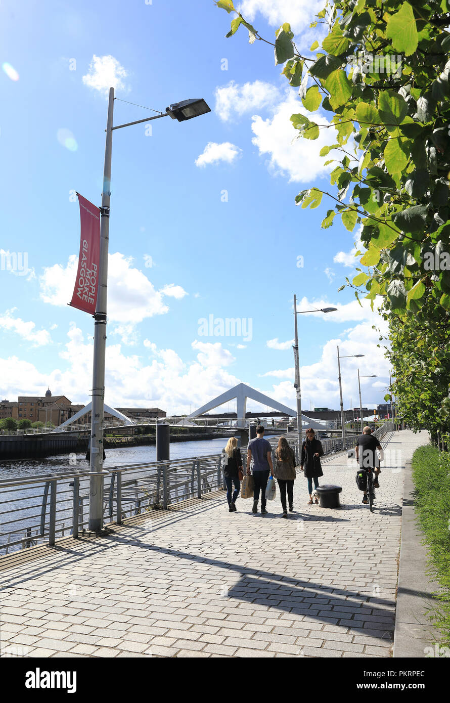 Walking and cycling on the towpath of the River Clyde, towards the Squiggly Bridge, in Glasgow, in Scotland, UK - Stock Image