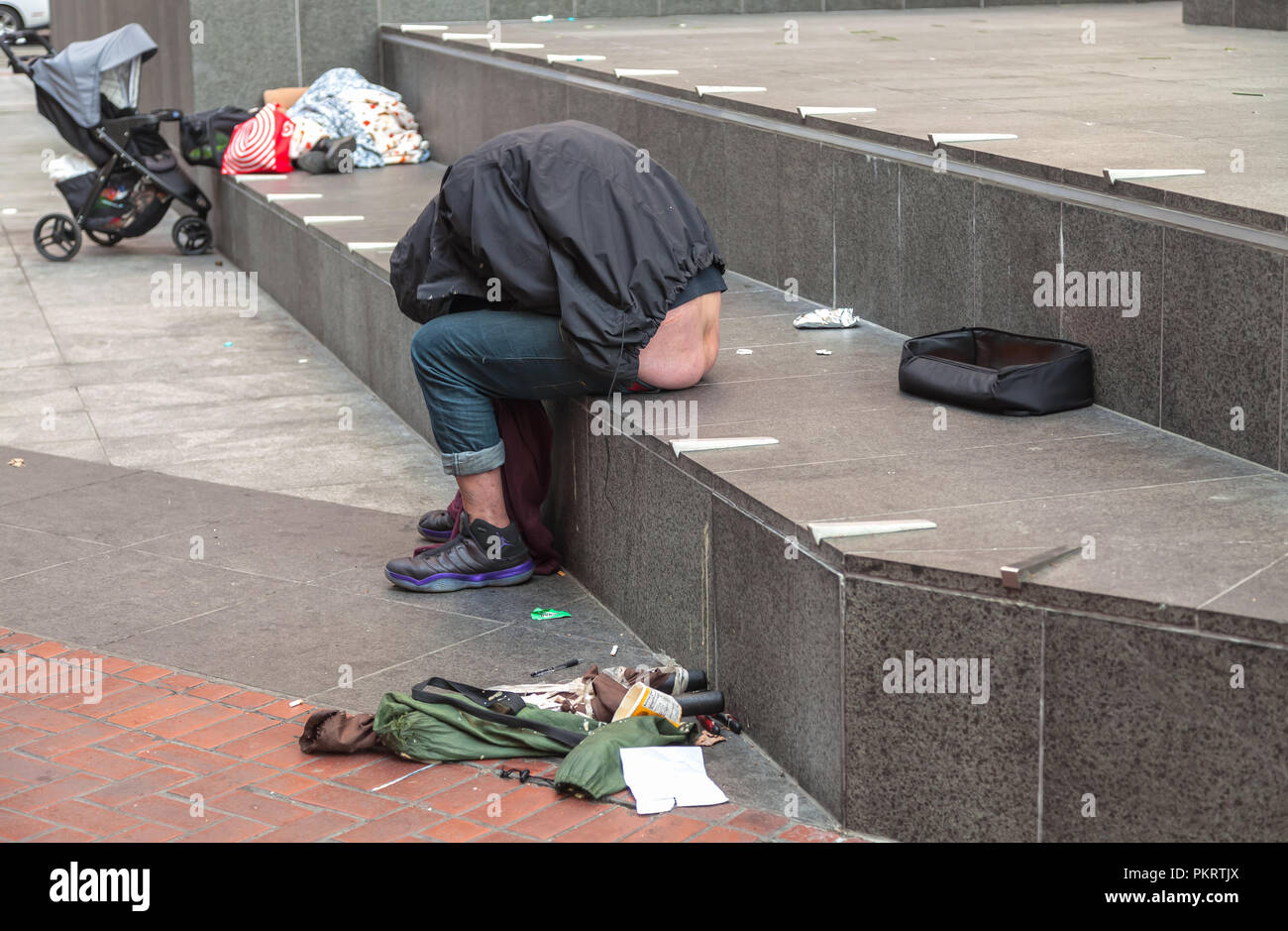 A homeless man sleeps on the street curb in San Francisco, California, United States. - Stock Image