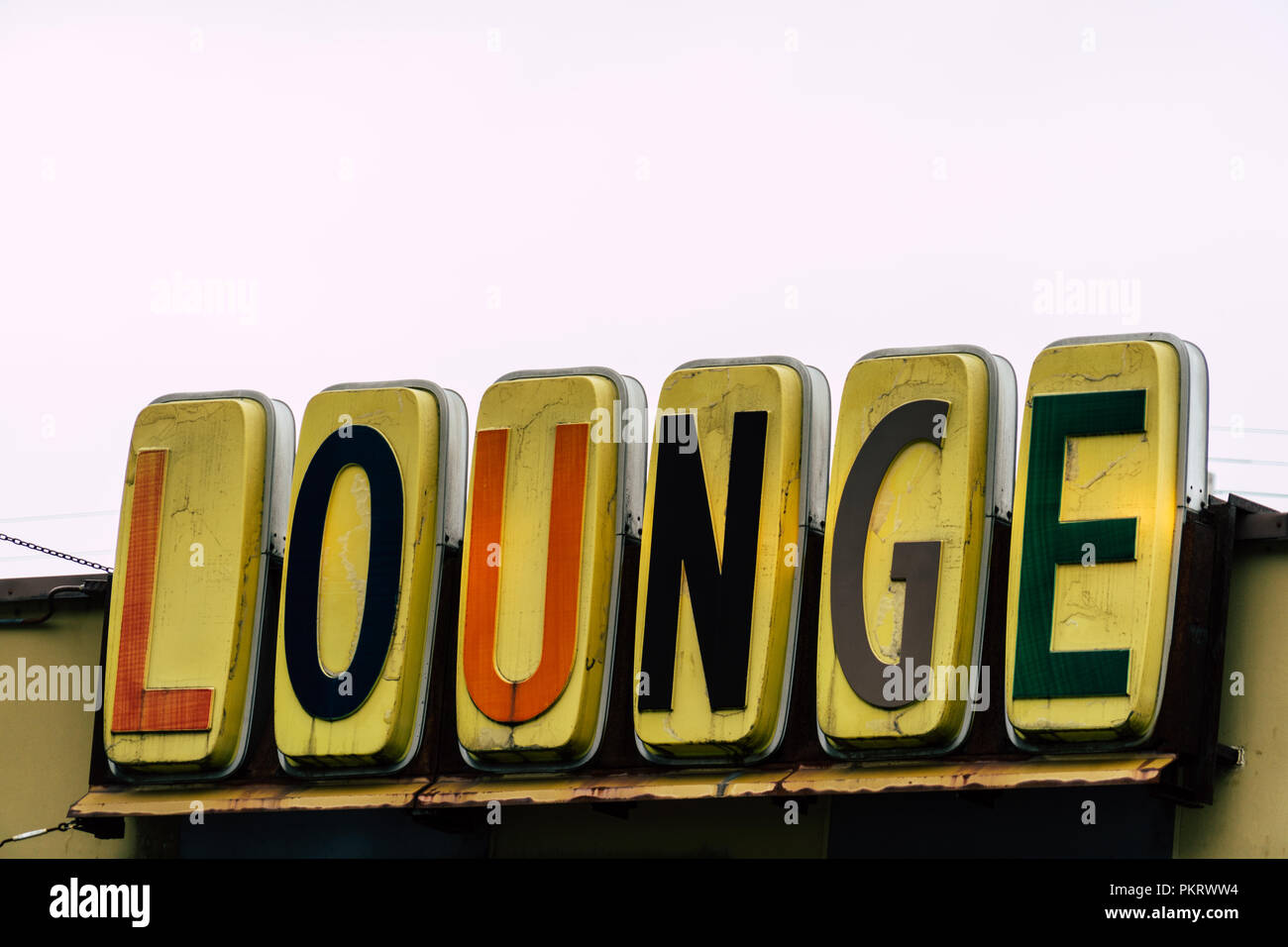 Generic lounge sign with mid century typeface font on overcast day - Stock Image