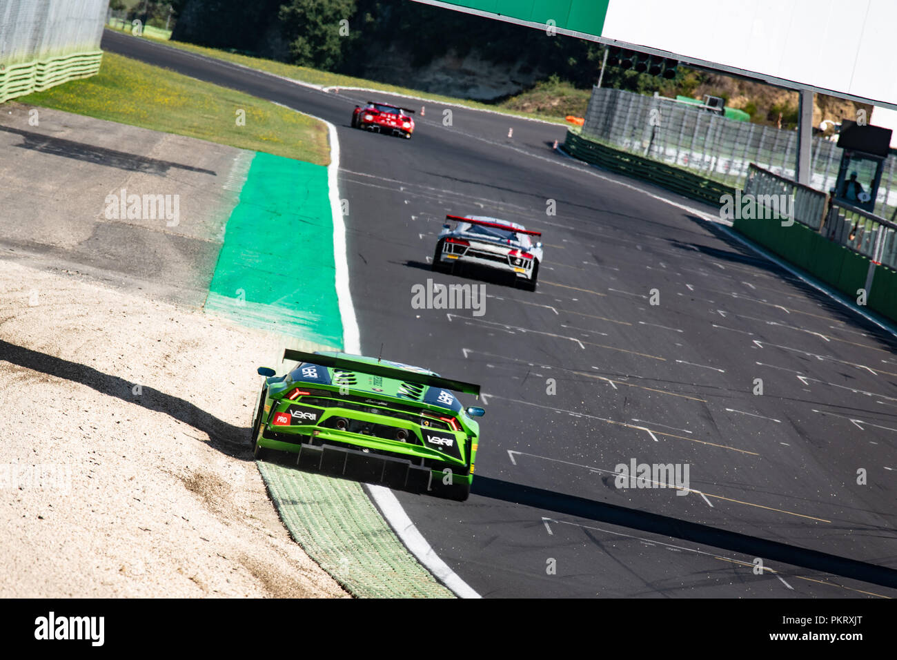 Wide shot of Lamborghini touring car in action rear view out of the corners in racing circuit - Stock Image