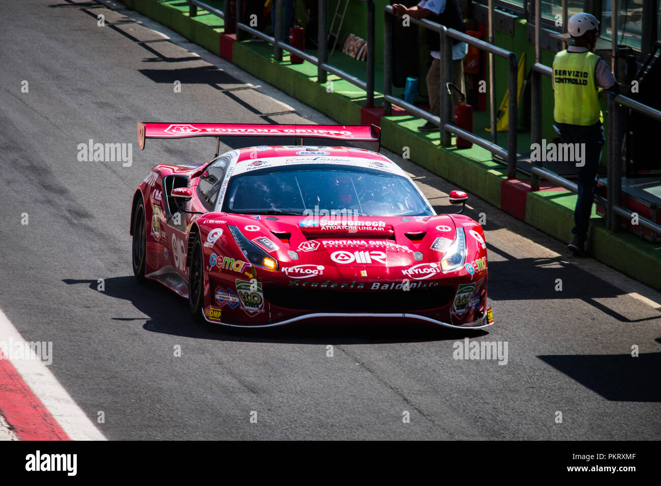 High angle view full length of Ferrari touring car in racing circuit pit lane - Stock Image