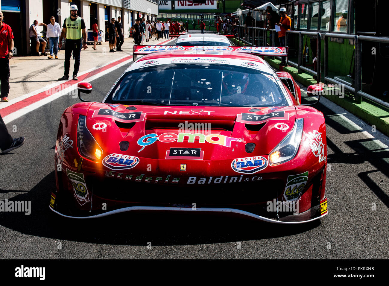 Front view full length of Ferrari touring car in racing circuit pit lane - Stock Image