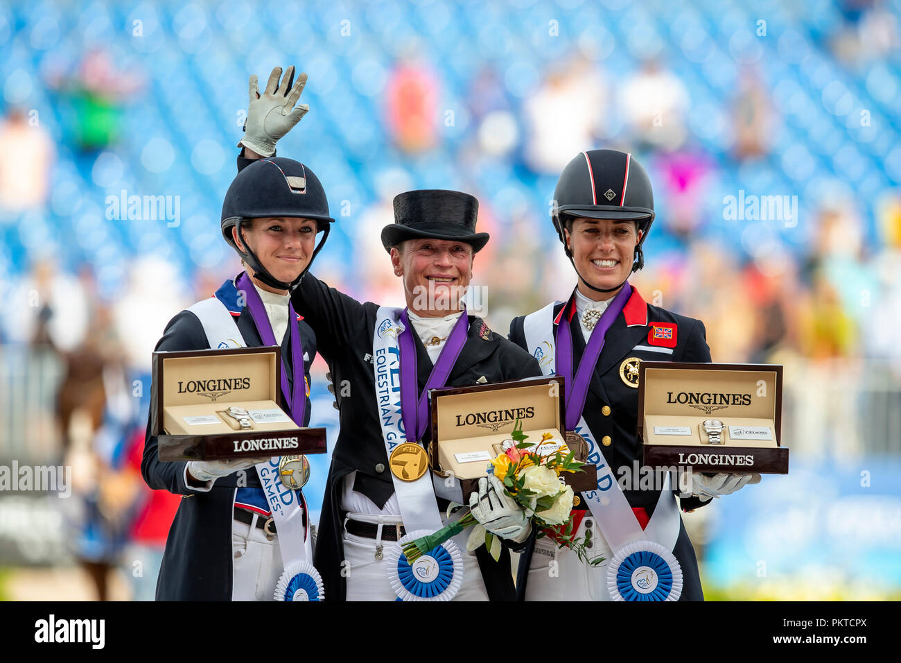 Tryon, USA. 14th Sep, 2018. Reiten, FEI World Equestrian Game 2018, Grand Prix Special: Winner Isabell Werth (M) from Germany cheers with second-placed Laura Graves from the USA (l) and third-placed Charlotte Dujardin from Great Britain on the podium. Credit: Stefan Lafrentz/dpa/Alamy Live News - Stock Image