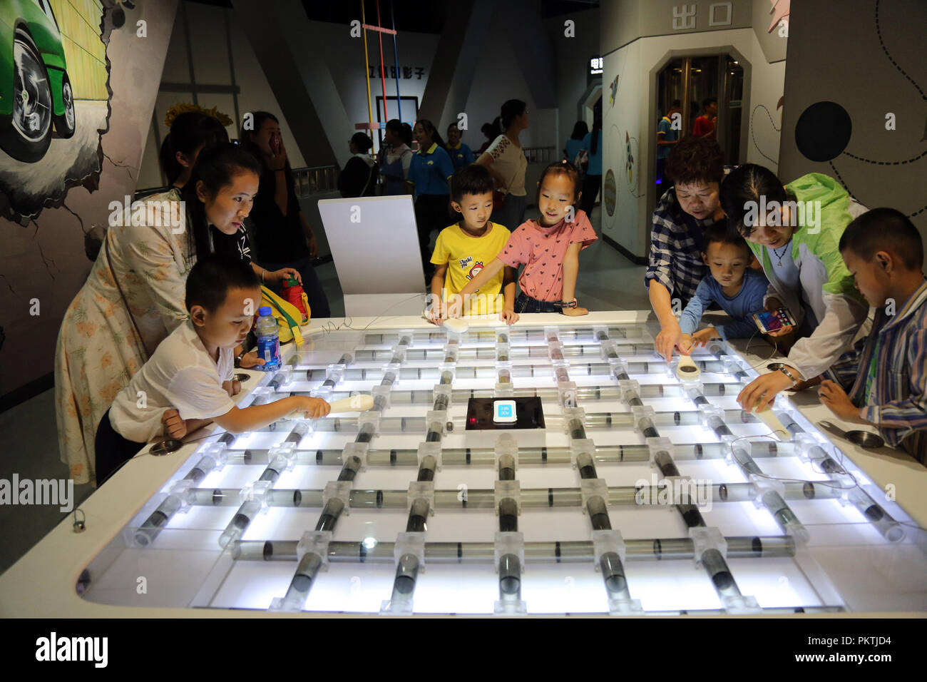 (180915) -- BINZHOU, Sept. 15, 2018 (Xinhua) -- Children accompanied by their parents learn about optics knowledge at Science and Technology Museum in Binzhou, east China's Shandong Province, Sept. 15, 2018. Various activities are scheduled to be held from Sept. 15 to Sept. 21 across China to greet the 2018 National Science Day held each year. (Xinhua/Chen Bin) (sxk) - Stock Image