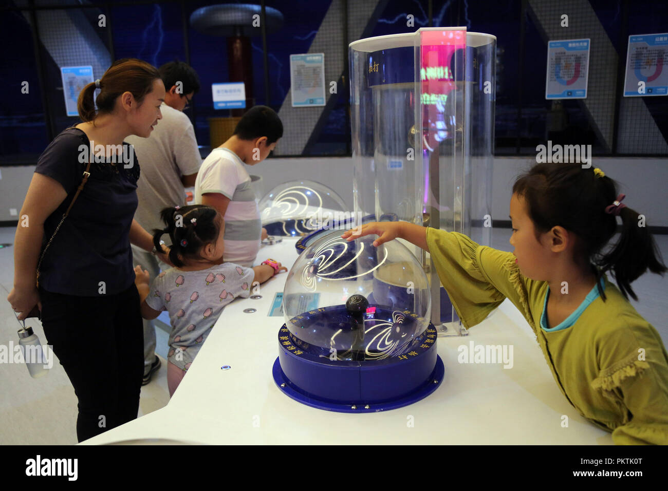 Binzhou, China's Shandong Province. 15th Sep, 2018. Children accompanied by their parents experience electromagnetic devices at Science and Technology Museum in Binzhou, east China's Shandong Province, Sept. 15, 2018. Various activities are scheduled to be held from Sept. 15 to Sept. 21 across China to greet the 2018 National Science Day held each year. Credit: Chen Bin/Xinhua/Alamy Live News - Stock Image